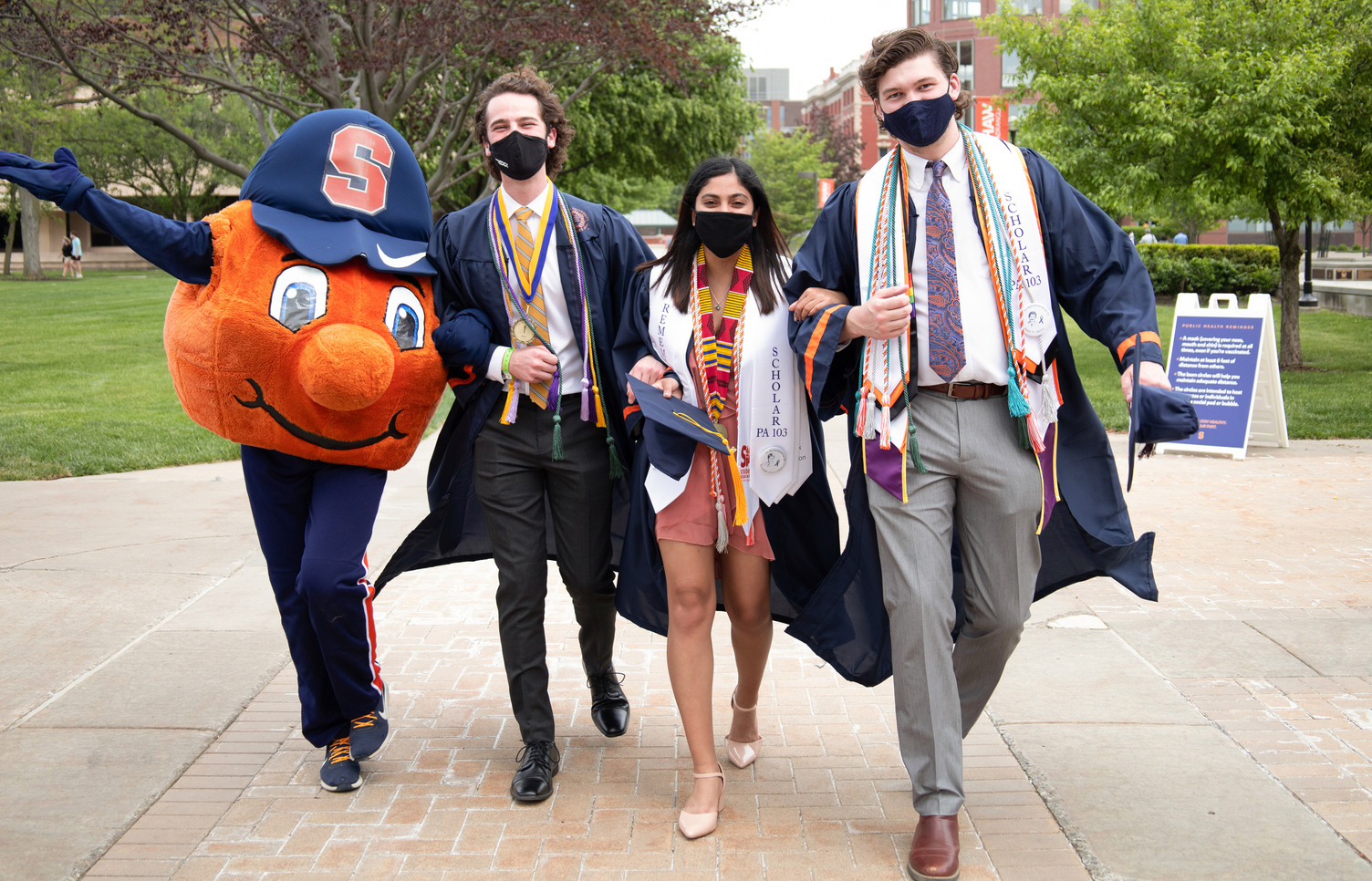 three students walking outside with Otto during Commencement