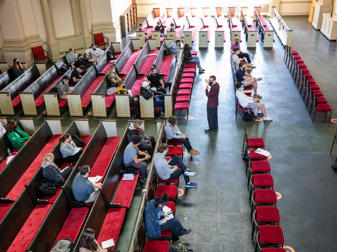 people seated in Hendricks Chapel with person standing in aisle
