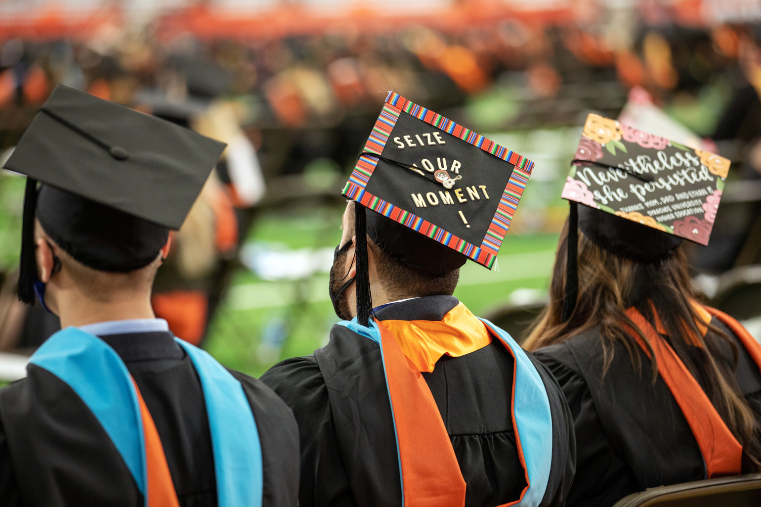 three graduates wearing caps that say Seize Your Moment and Nevertheless she persisted