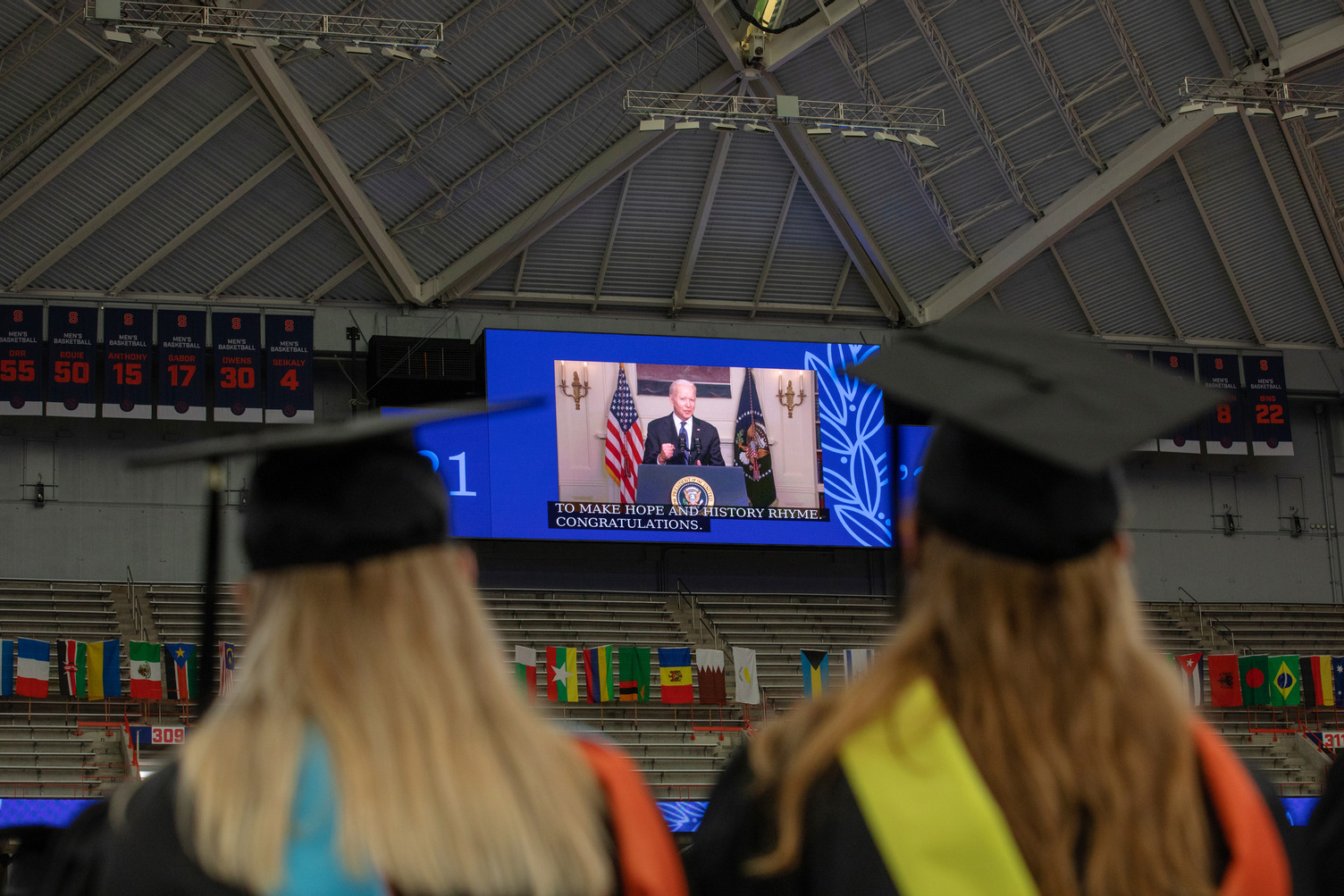 two students in caps and gowns watching a screen with President Joe Biden during Commencement 2021