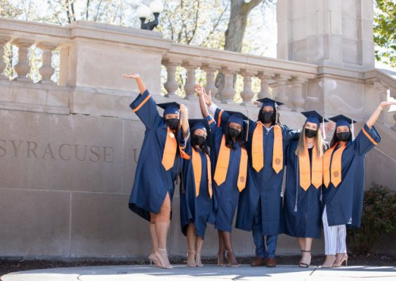 people standing on campus in graduation cap and gowns