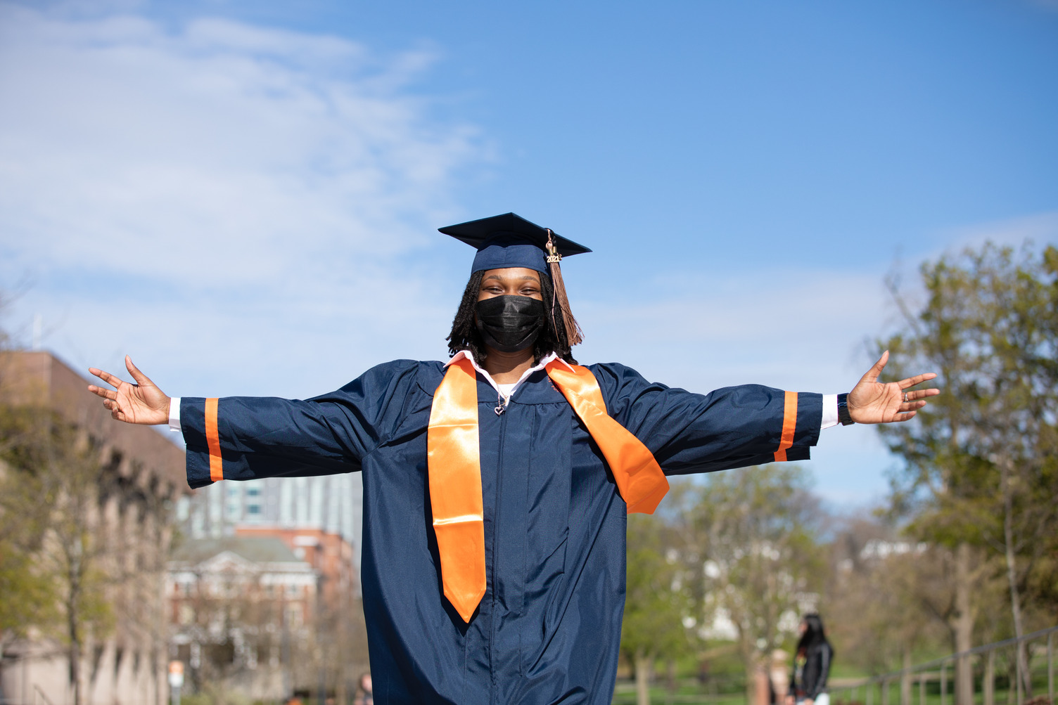 student in cap and gown stands with arms outstretched outside during Commencement 2021