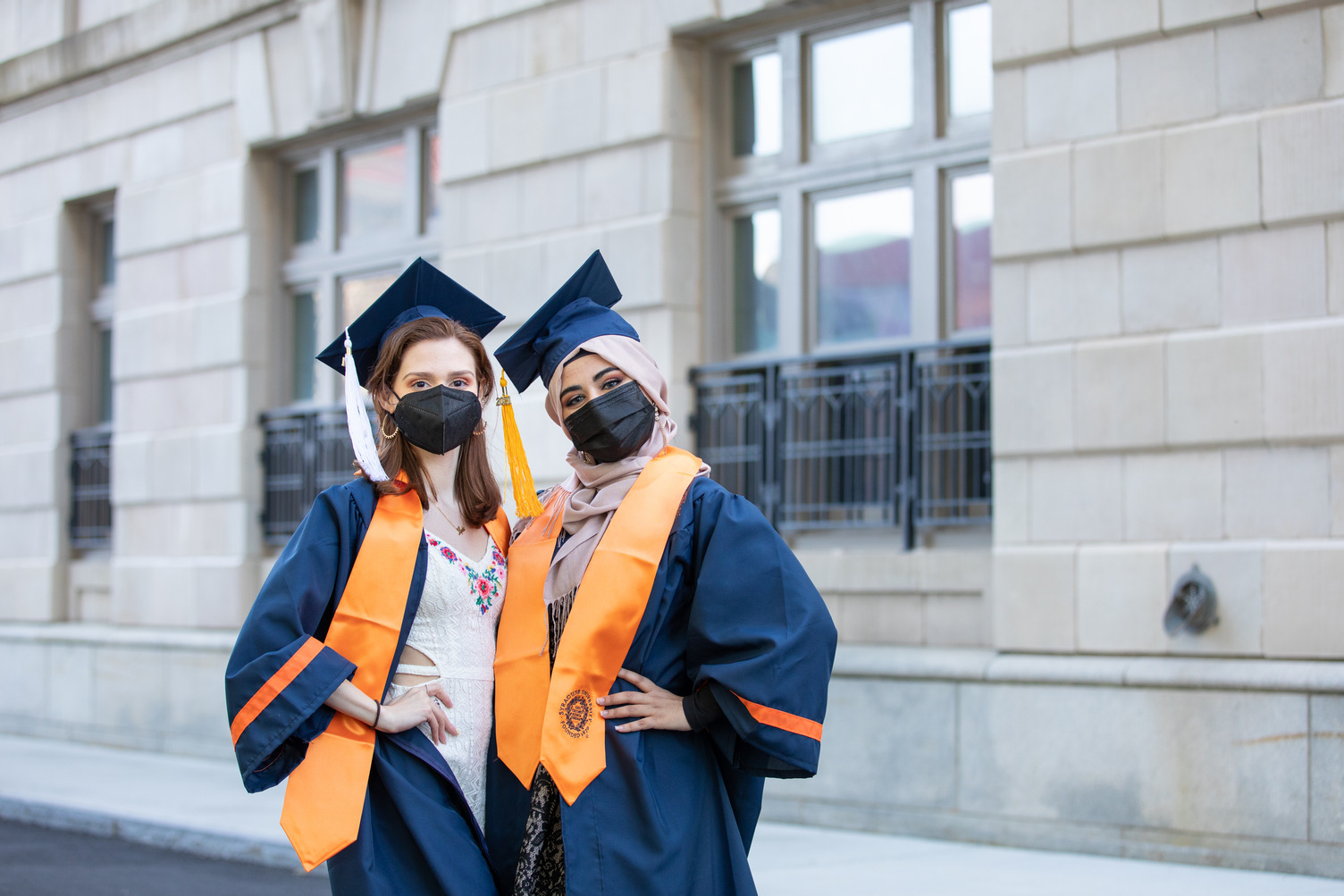 two students posing together in their caps and gowns