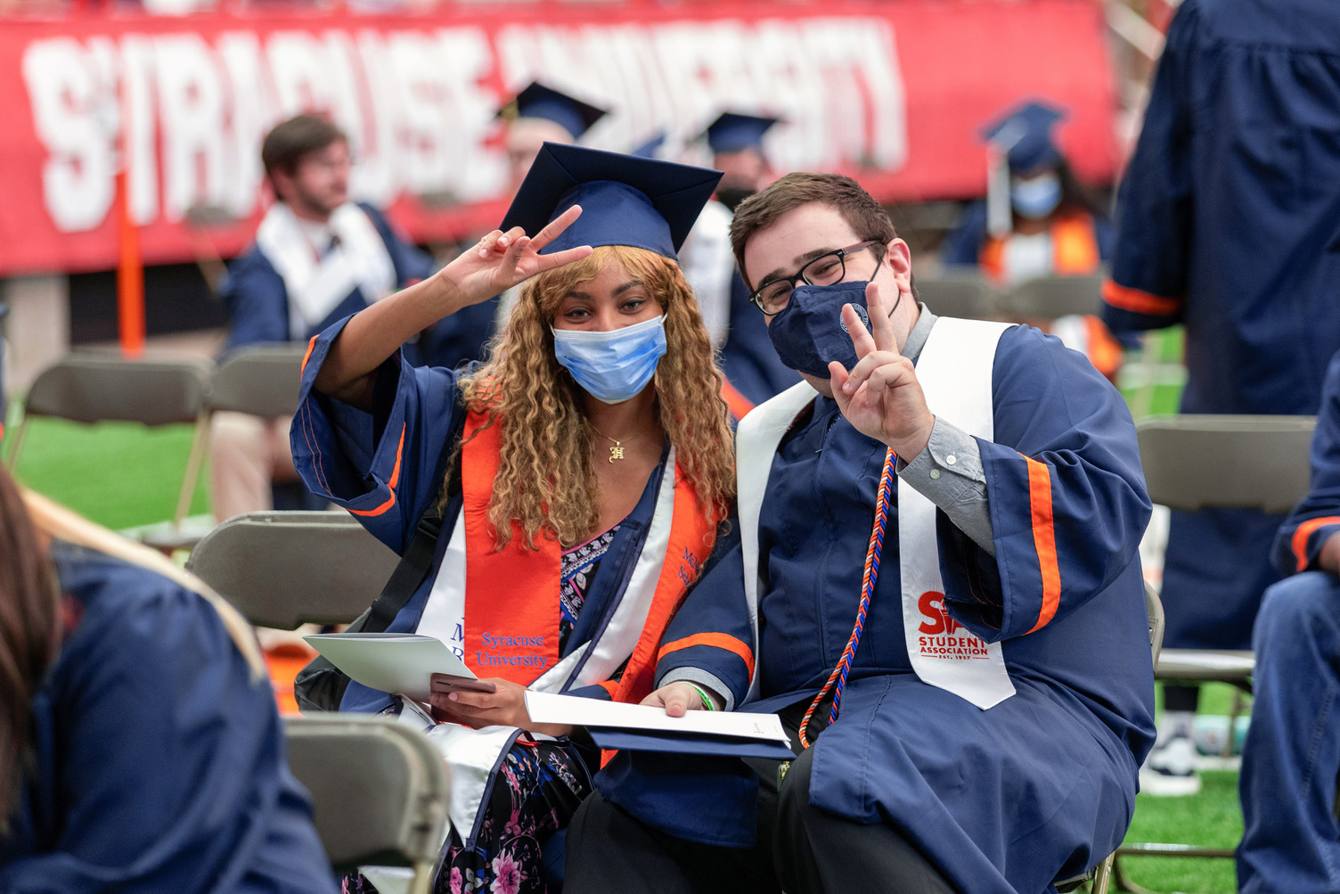 two students hold up peace fingers at Commencement 2021