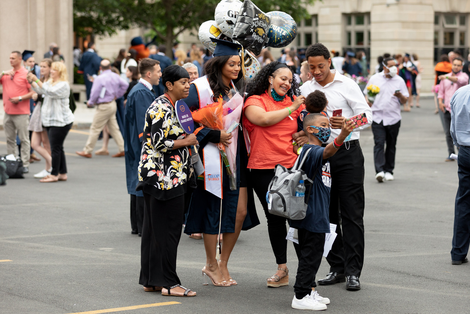a graduate and their family celebrating and taking photos outside