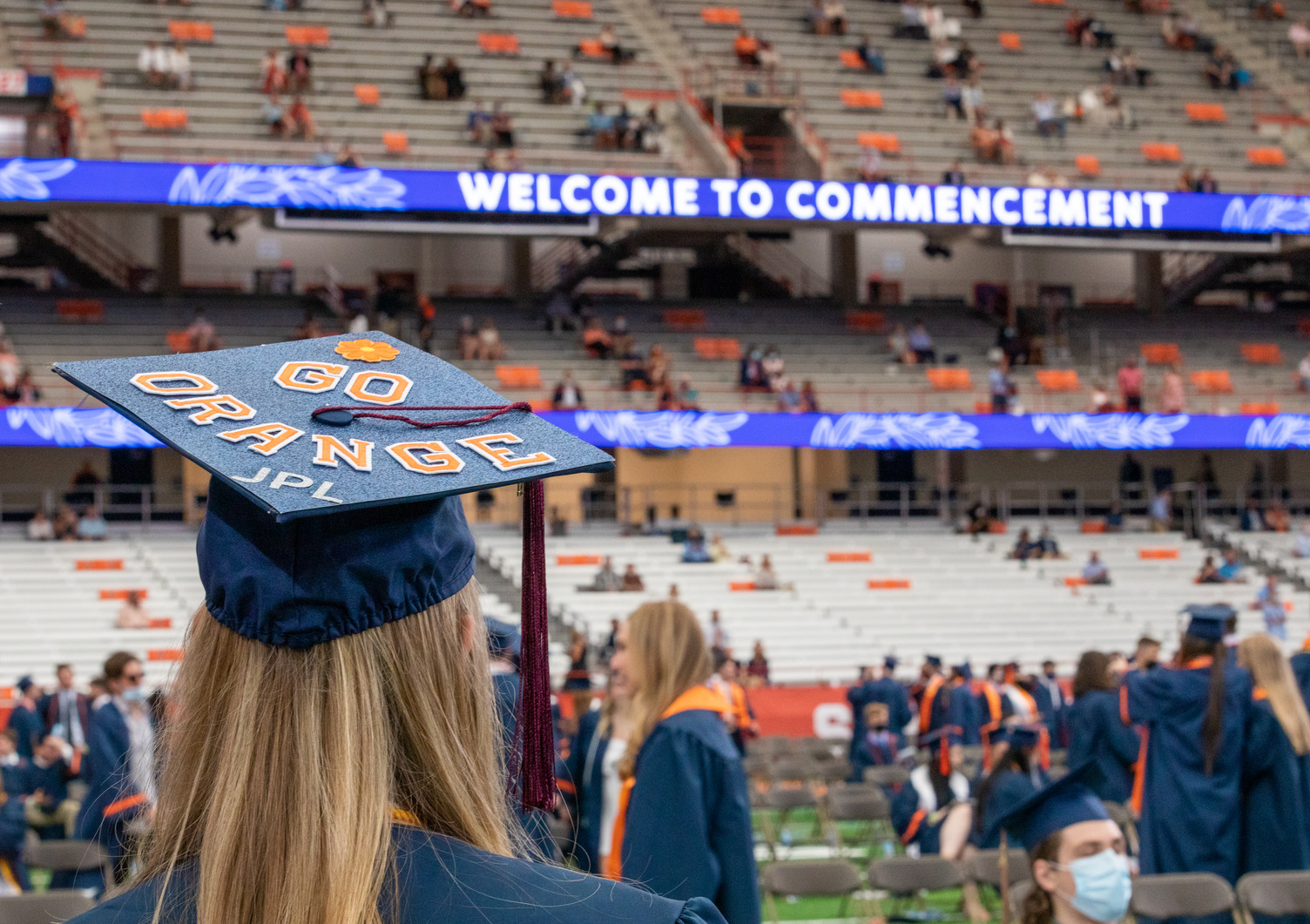 a graduate whose hat says GO ORANGE in the stadium for Commencement 2021
