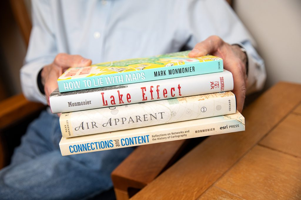 person holding four books