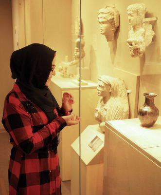Nidaa Aljabbarin at MoMA looking at an exhibit of a vase