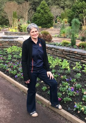 Connie Caldwell posing near a flower bed