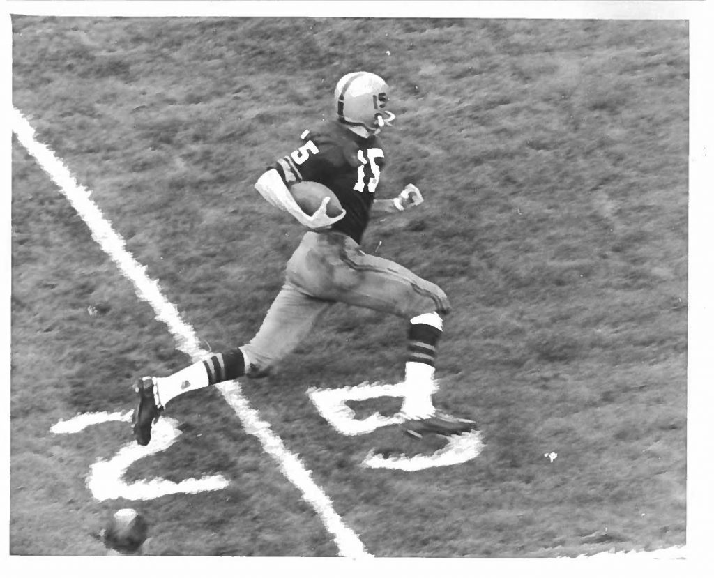 person in athletic uniform running with football