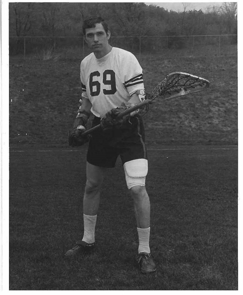 person in sports uniform holding lacrosse stick