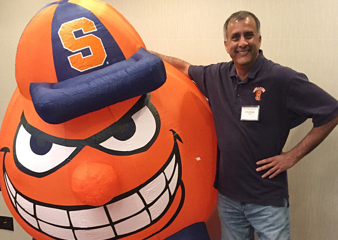 person standing next to inflatable of Otto the Orange
