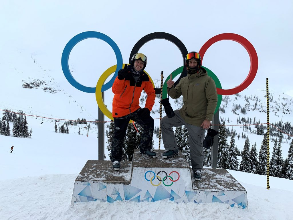 two people outdoors in front of Olympic rings