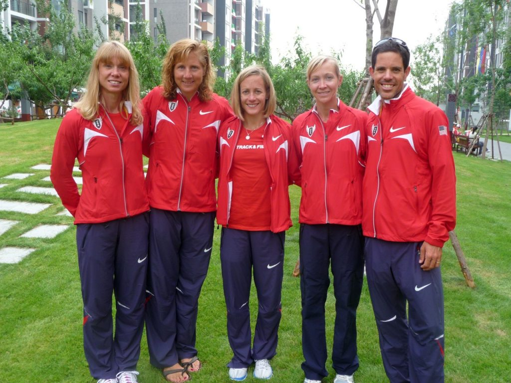 Kimberly Keenan-Kirkpatrick poses with four long-distance runners