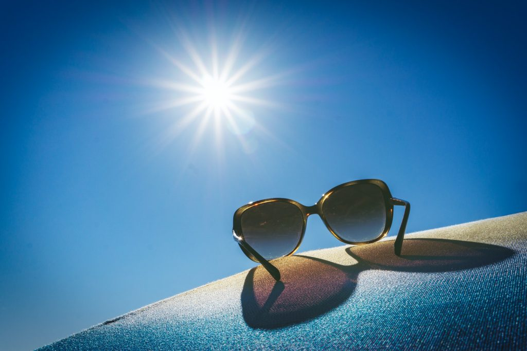sunglasses resting with sun in background