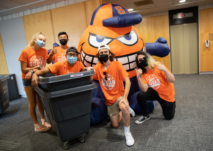 students pose with move-in bins with inflatable Otto the Orange