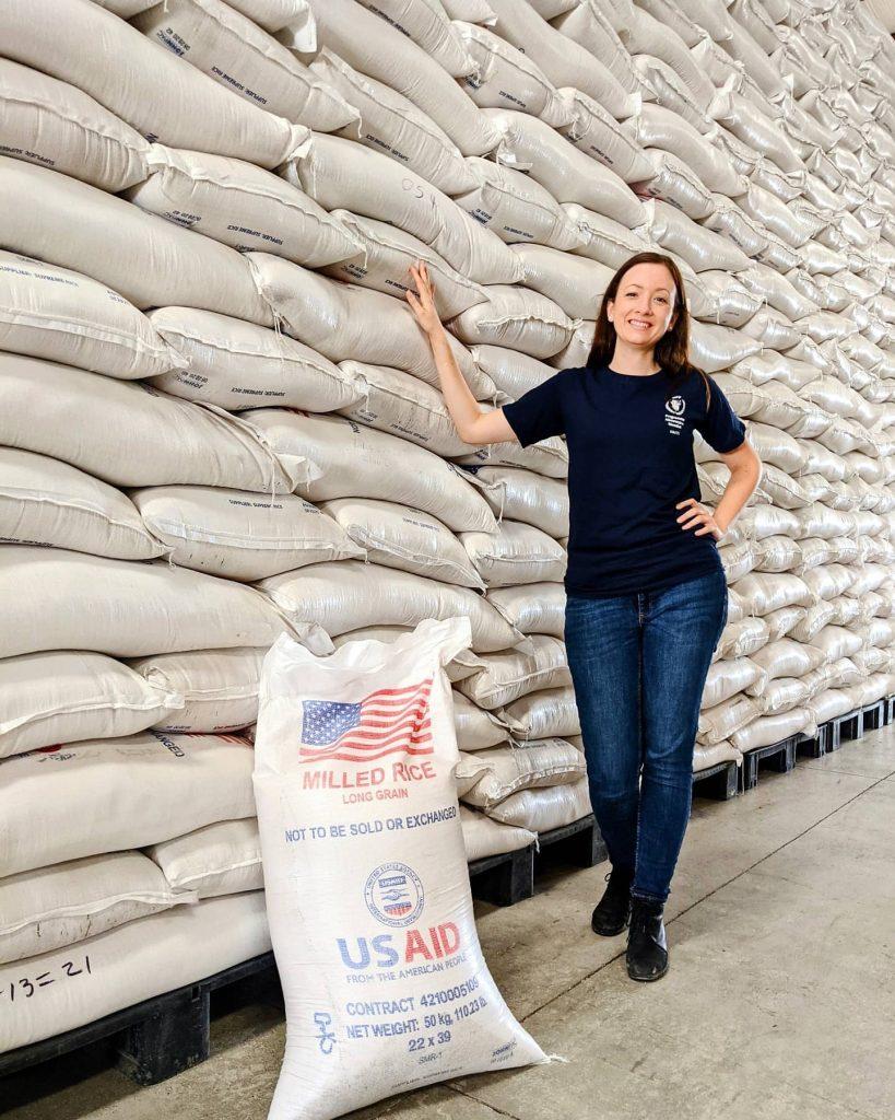 Megan Sullivan in front of bags of rice