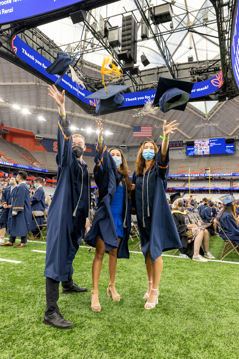 three graduates throwing their caps in the air during Commencement 2020