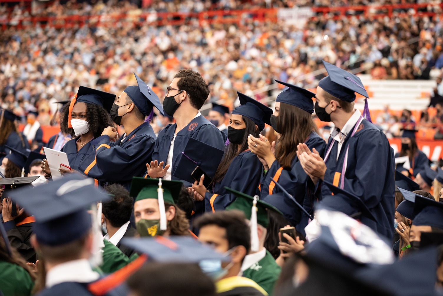 crowd of people with several standing and clapping at Commencement 2020