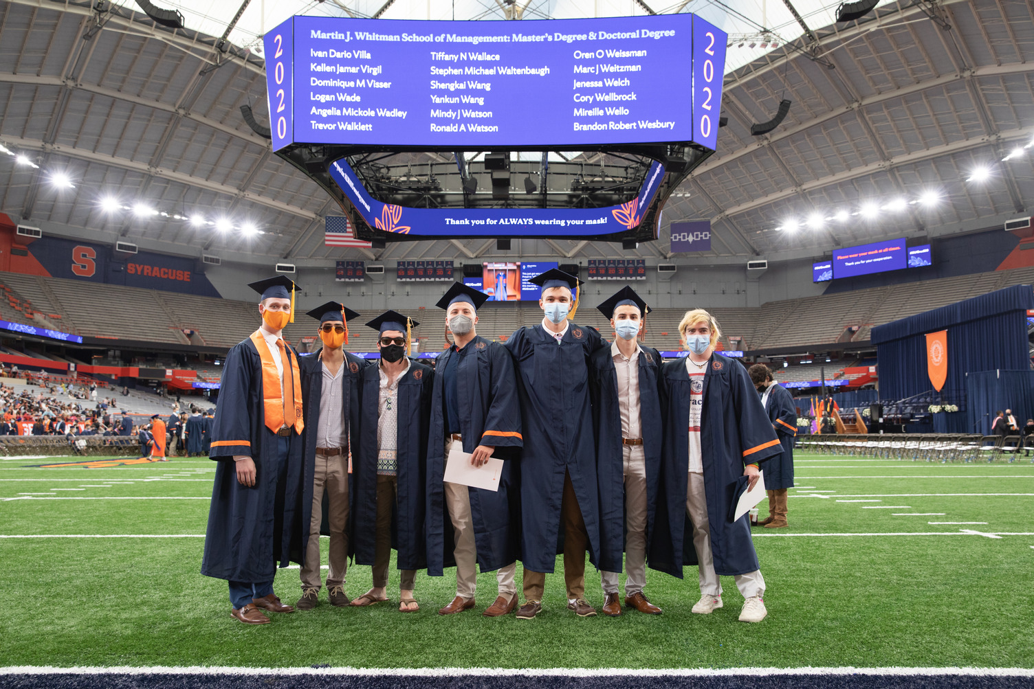 a group of seven participants in Commencement 2020 on the field of the stadium