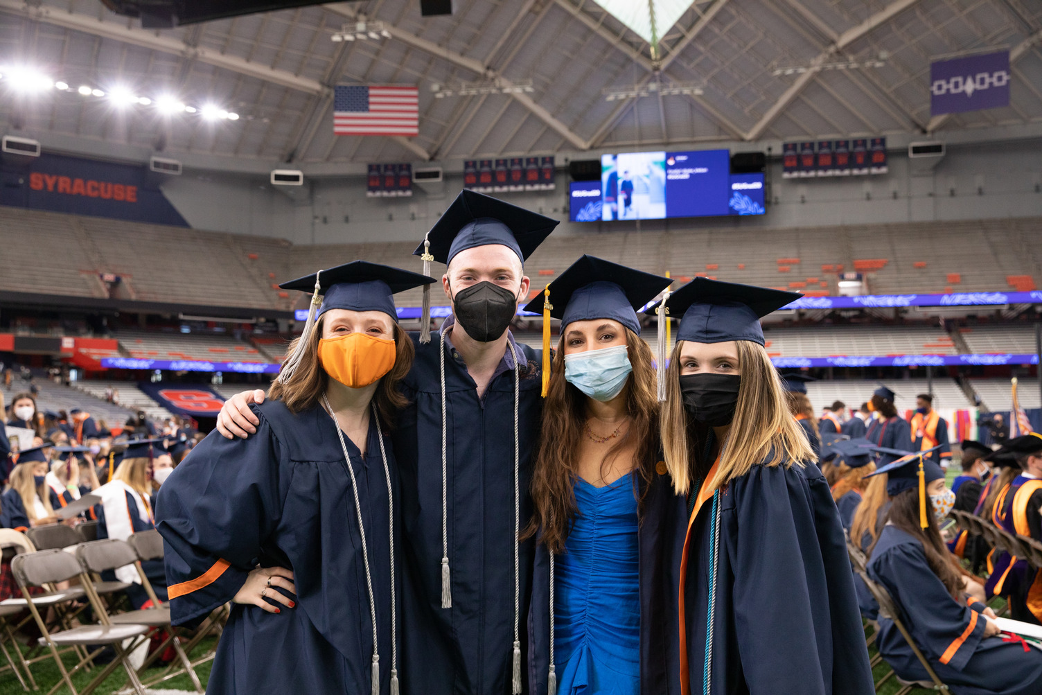 four people in caps and gowns at Commencement 2020 on Sept. 19, 2021, in the stadium