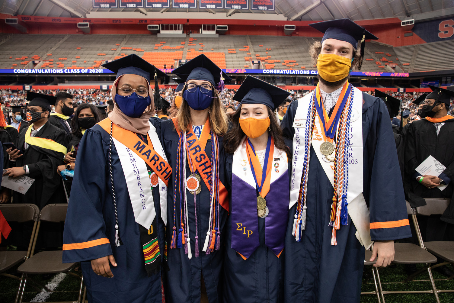 four people pose in caps, gowns and an assortment of regalia at Commencement 2020, held Sept. 19, 2021 in the stadium