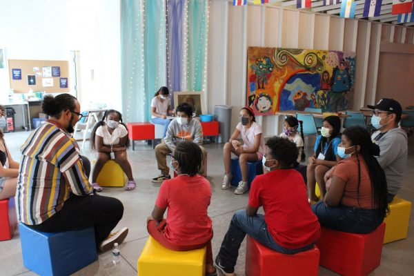 group of children and SU alumni and faculty during a reading program at La Casita