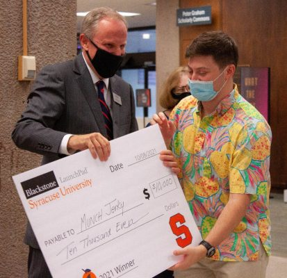 Whitman student Selim Dangoor recceives a prize check from Syracuse University Libraries Dean David Seaman at 'Cuse Tank 2021