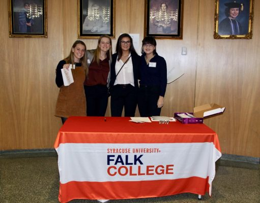 four students standing at a table with a Falk College tablecloth at a 2019 alumni panel event
